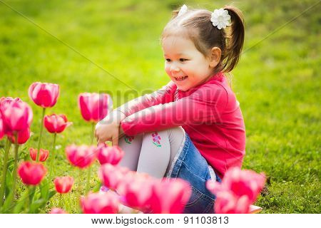 Cheerful Little Girl Sitting In Grass Looking At Tulips