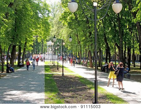 Townsfolk Having A Walk In The City Park At A Sunny Feast Day
