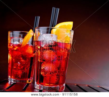 Spritz Aperitif Aperol Cocktail With Orange Slices And Ice Cubes On Color Gradient Background