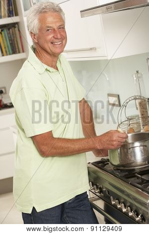 Senior Man Preparing Meal At Cooker
