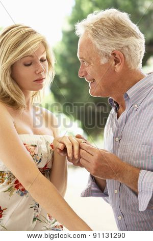 Older Man Proposing To Younger Woman