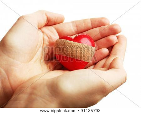 Female hands holding heart with plaster isolated on white