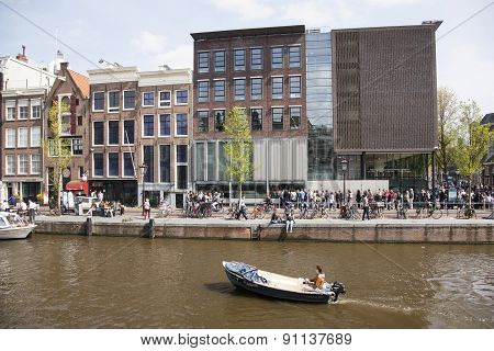 Small Boat In Front Of Anne Frank House In Amsterdam Canal In Spring