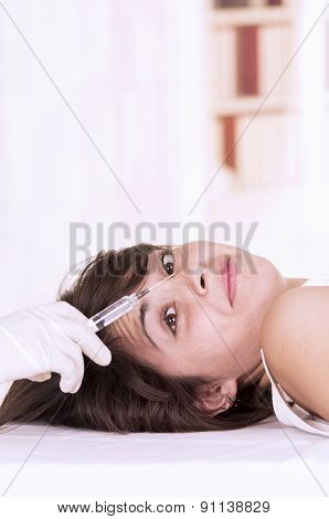 Young girl lying down ready to get a cosmetic injection in her face