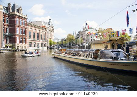 Tourists Board Canal Boat In Centre Of Amsterdam