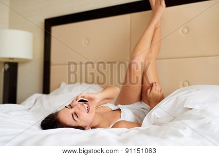 Woman Lying Upside Down In Bed Talking On Cell Phone.