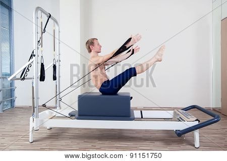 Pilates reformer workout exercises man at gym indoor