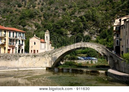bridge over the nervia river in dolceacqua italy. the bridge was made famous by claude monet who traveled to dolceacqua and featured it in a painting. poster