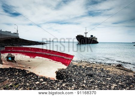 boat on the backgrond with old broken agrounded ship , Lanzarote, Canary Islands, Spain