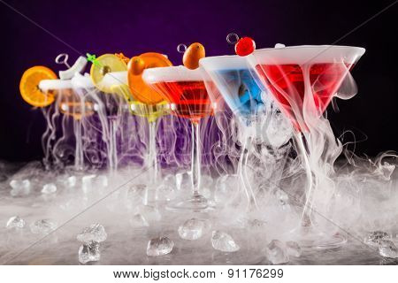 Martini drinks with dry ice smoke effect, served on bar counter with dark colored background