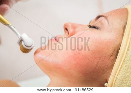 Medical cosmetic procedure. Mikronidling. Beautician performs Dermaroller procedure.young beautiful woman having an injection mesotherapy. cosmetic procedures in spa clinic. poster
