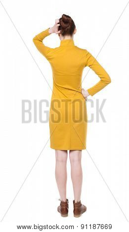 back view of young beautiful  woman scratching his head. backside view of person.  Isolated over white background. Girl in mustard strict dress thoughtfully scratching his head with his left hand.