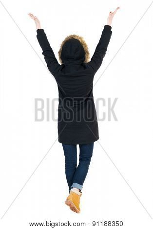 Back view Beautiful woman in parka looking at wall and Holds  hand up.  Rear view people. Isolated over white background. Young woman in prayer. Girl in winter jacket with hood commended hands to sky.