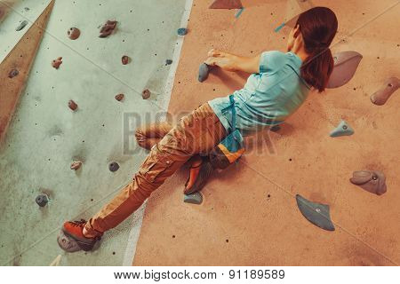 Free climber young woman climbing artificial boulder indoor. Focus on hands poster