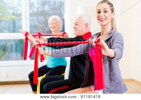 People, young and senior, at gym exercise with stretch band