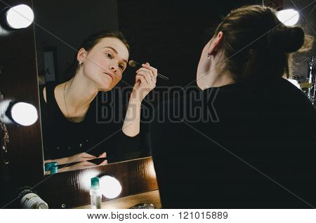 Young beautiful woman applying her make up face with brush, looking in a mirror, sitting on chair at