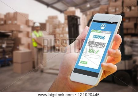 Hand holding smartphone against warehouse worker loading up pallet