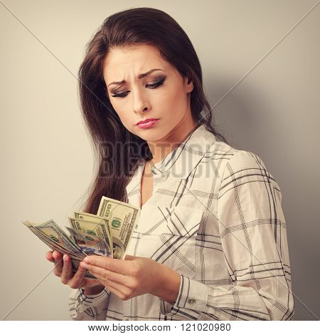 Beautiful young unhappy woman looking on dollars and thinking how little money she have earned and h