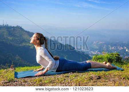 Beautiful sporty fit woman practices yoga asana bhujangasana - cobra pose beginner variation outdoors in mountains in the morning