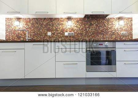 Domestic kitchen with white units, mosaic wall, oven, water tap