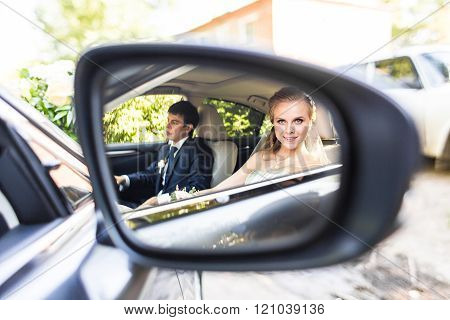 Bride and groom inside a  car. They are happy.