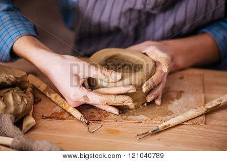 Closeup of clay pot making by hands of young woman in pottery workshop