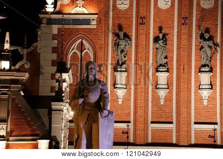 The sculptures on the facade of the Blackheads House at night. Riga Latvia