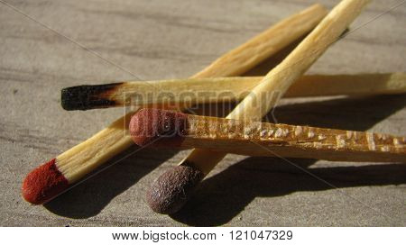 Versicolor matches ready to burn on wooden table.