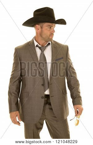 A cowboy standing in his suit with his cowboy hat on.
