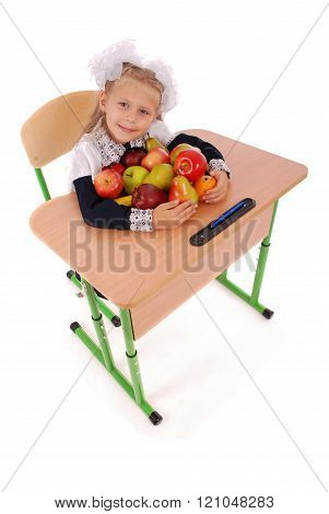 Little Schoolgirl Sitting At A Desk Holding A Lot Of Fruits