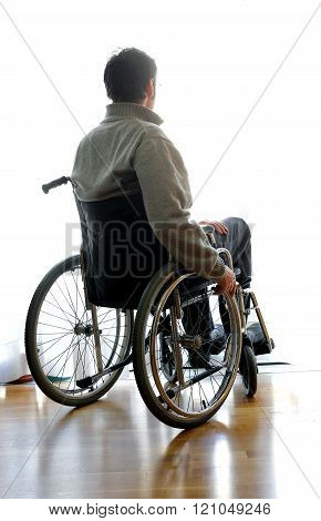 Disabled Sitting In A Wheelchair In The Room Near The Window