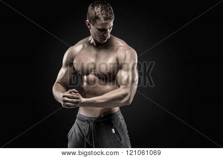 Stunning muscular man showing perfect shoulders, biceps, triceps, chest