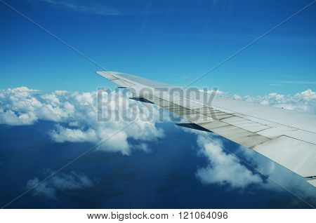 View from airplane window. Wing of an airplane flying above the clouds over tropical island.