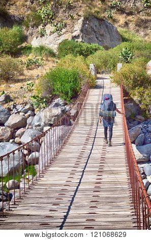hiker with backpack crossing bridge