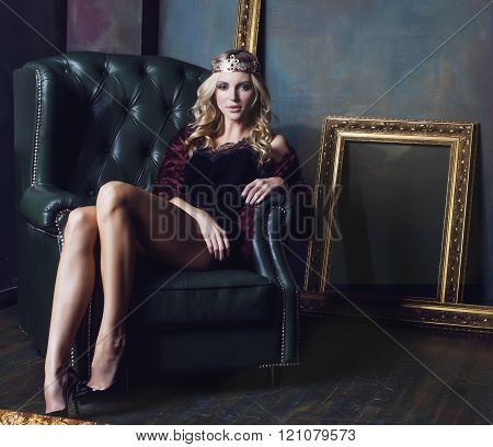 young blond woman wearing crown in fairy luxury interior with empty antique frames total wealth