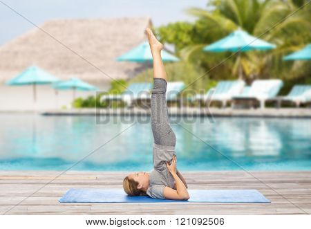fitness, sport, people and healthy lifestyle concept - woman making yoga in shoulderstand pose on mat over beach and swimming pool background