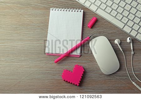 Computer peripherals with pink heart, pen and notebook on wooden table