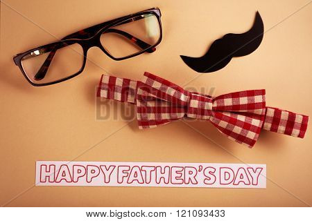 Happy fathers day sticker, bow tie, glasses, mustache on beige background