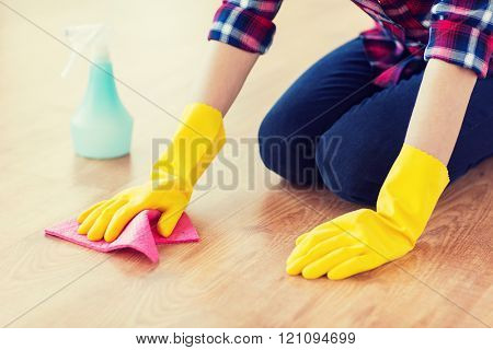 people, housework and housekeeping concept - close up of woman in rubber glover with cloth and detergent spray cleaning floor at home