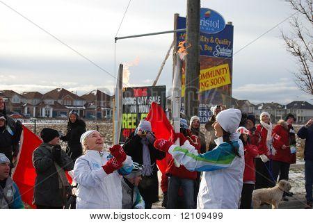 MILTON, Canadá - el 19 de diciembre: Paso de la llama entre dos portadores de la antorcha durante la Torc Olímpico