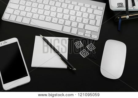 Workplace with mobile phone, computer peripherals and stationery on black table