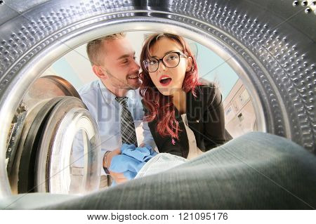 Happy Couple Doing Laundry seen from inside washing machine
