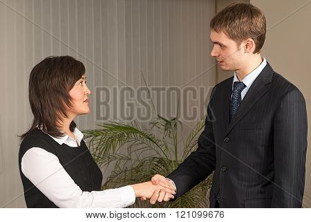 Business man and woman handshake in office