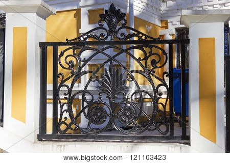 Iron fence in front of the yellow house