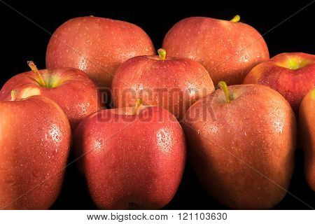 Fresh apples with water droplets on black.