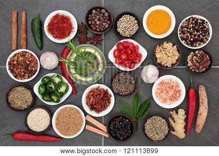 Large herb and spice food seasoning sampler with olive oil over distressed grey slate tile background.