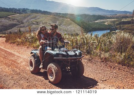 Happy Couple Riding On A Quad Bike