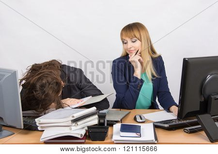 Female Colleagues In The Office, One Had Fallen Asleep On A Pile Of Folders, The Second With A Sneer