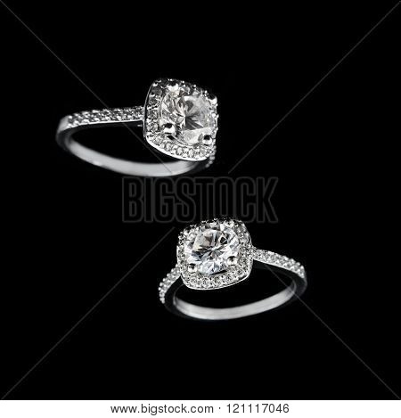 Luxury jewellery. White gold or silver engagement rings with diamonds closeup on black background. S