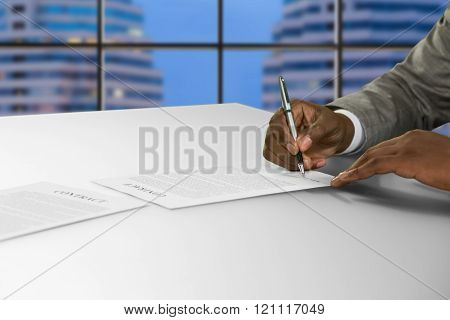 Afroamerican signs document at office.